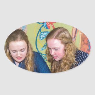 Two students learning with books in biology lesson oval sticker