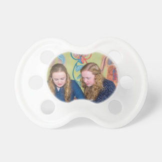Two students learning with books in biology lesson pacifier