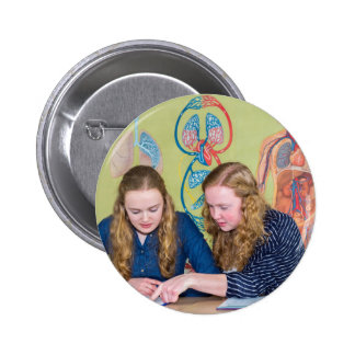 Two students learning with books in biology lesson pinback button