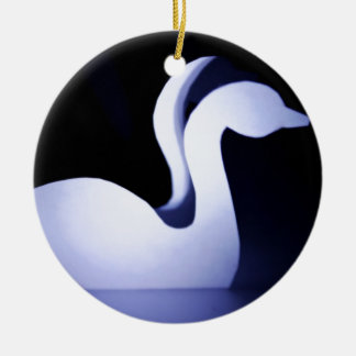 Two swans cut from a paper on a dark background ceramic ornament