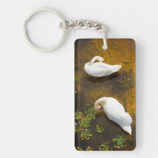 Two swans with sun reflection on shallow water. keychain