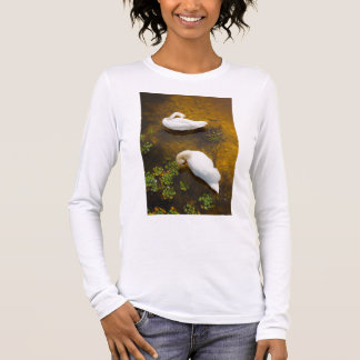 Two swans with sun reflection on shallow water. long sleeve T-Shirt