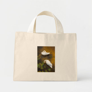 Two swans with sun reflection on shallow water. mini tote bag