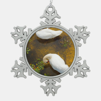 Two swans with sun reflection on shallow water. snowflake pewter christmas ornament