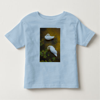 Two swans with sun reflection on shallow water. toddler t-shirt