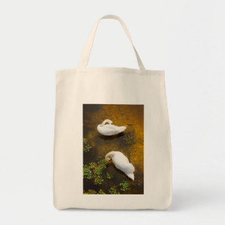 Two swans with sun reflection on shallow water. tote bag