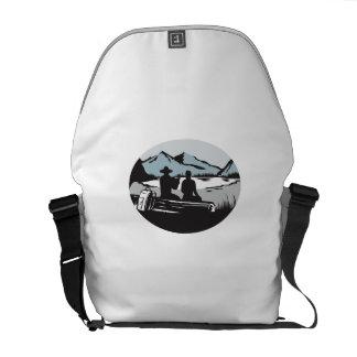 Two Trampers Sitting on Log Lake Mountain Oval Woo Messenger Bag