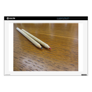 Two used colored pencils on wooden table decal for laptop