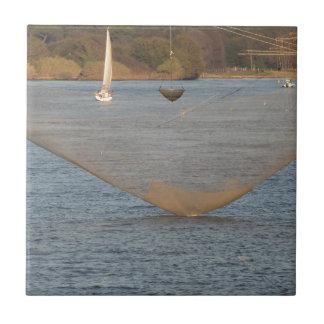 Typical italian fishing net along the river ceramic tile