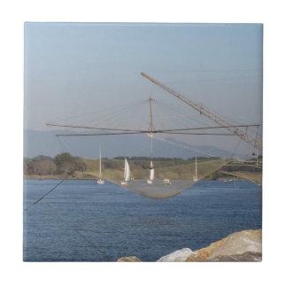 Typical italian fishing net along the river tile