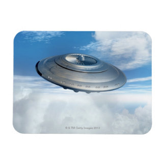 UFO flying through cloudy skies. Magnet