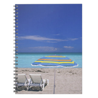 Umbrella and two lounge chairs on beach, Miami Notebook