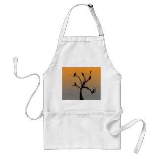 Un árbol desnudo con las siluetas de cuervos delantal