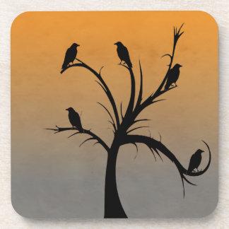 Un árbol desnudo con las siluetas de cuervos posavasos