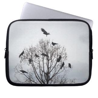 Un árbol en el cual muchos cuervos tienen resto funda ordendadores