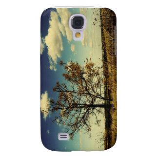 Un árbol solo en un campo seco amarillo