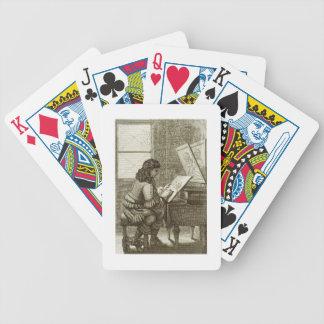 Un artista que copia sobre una placa del grabado,  barajas de cartas