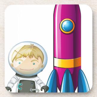 Un astronauta al lado de un cohete posavaso