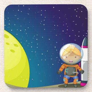 Un astronauta que se coloca al lado del cohete posavasos de bebidas