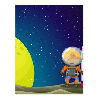 Un astronauta que se coloca al lado del cohete tarjeta postal