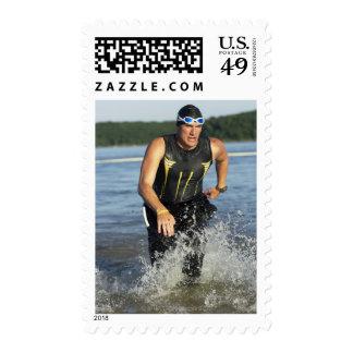 Un athelete masculino que corre del agua mientras estampilla