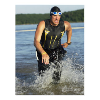 Un athelete masculino que corre del agua mientras postal