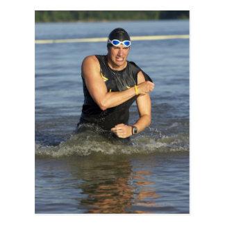 Un athelete masculino que corre del agua mientras postales