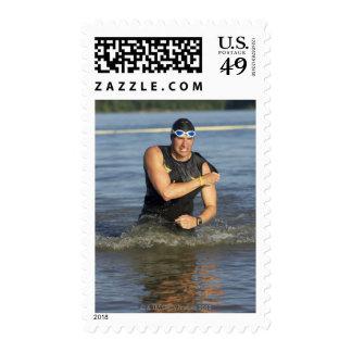 Un athelete masculino que corre del agua mientras sellos postales