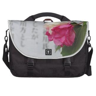 Un blanco, una flor rosada y caracteres japoneses bolsas para portátil