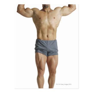 un bodybuilder masculino caucásico adulto sostiene tarjeta postal