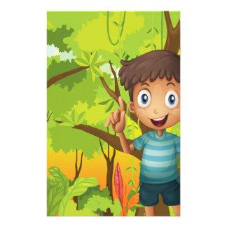 Un bosque con un muchacho joven que lleva una papelería personalizada