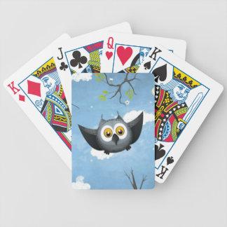 Un búho gris lindo baraja cartas de poker