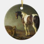 Un caballo con una silla de montar al lado de ella ornamento de navidad