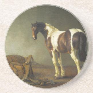 Un caballo con una silla de montar al lado de ella posavasos manualidades