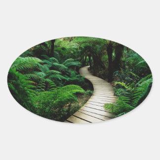 Un camino en el medio del bosque salvaje pegatina ovalada