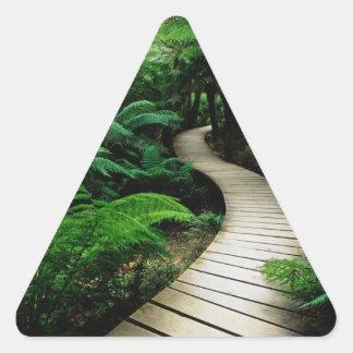 Un camino en el medio del bosque salvaje pegatina triangular