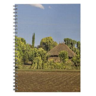 Un campo cultivado delante de casas de tejado cubi libro de apuntes