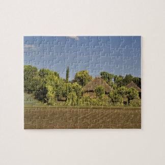 Un campo cultivado delante de casas de tejado cubi puzzle