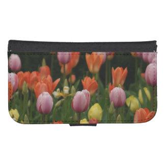 Un campo de peonies, de cyclamens y de tulipanes fundas billetera para teléfono