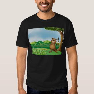 Un castor que sostiene un palillo debajo del árbol remera