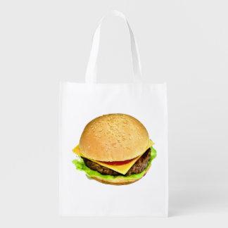 Un cheeseburger jugoso grande en un bollo de la bolsas para la compra