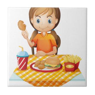 Un chica bonito que come en el restaurante de azulejos