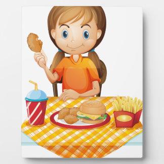 Un chica bonito que come en el restaurante de placas para mostrar