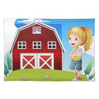 Un chica delante del barnhouse rojo en el hillto mantel individual
