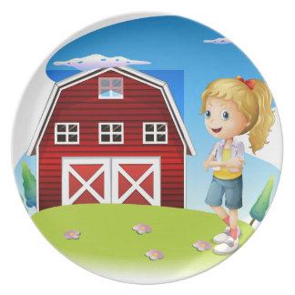 Un chica delante del barnhouse rojo en el hillto platos para fiestas