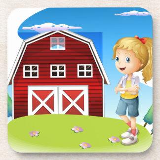 Un chica delante del barnhouse rojo en el hillto posavasos