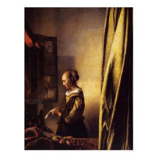 Un chica que lee una letra en una ventana abierta tarjetas postales