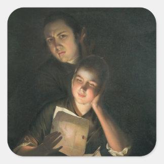 Un chica que lee una letra por luz de una vela pegatina cuadrada