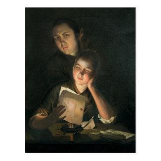 Un chica que lee una letra por luz de una vela tarjetas postales