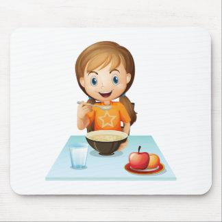Un chica sonriente que come su desayuno tapete de raton